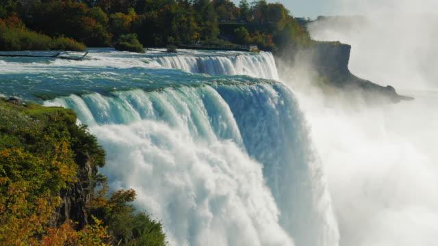 vídeos de stock, filmes e b-roll de a famosa cachoeira de niagara falls, um local popular entre turistas de todo o mundo. a vista do lado americano. na foto, um pode ver de uma vez de duas cachoeiras hq prores 422 10 bit vídeo - rio niagara