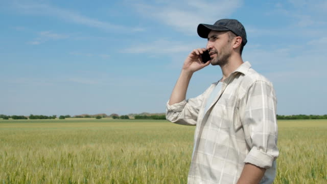 The farmer is talking on the phone.
