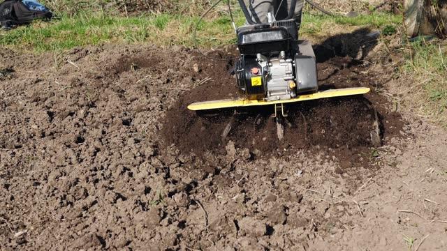 The farmer tills the soil using a rototiller, slow motion closeup. video