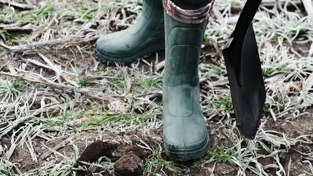 The farmer's legs in green rubber boots on. Gardening outfits, autumn rubber footwear.