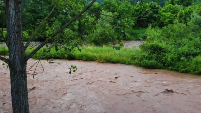 vídeos de stock, filmes e b-roll de o rio rápido flui através da aldeia e carrega tudo à sua frente - um rio rápido lamacento - chuvas fortes - desastre natural - multicóptero
