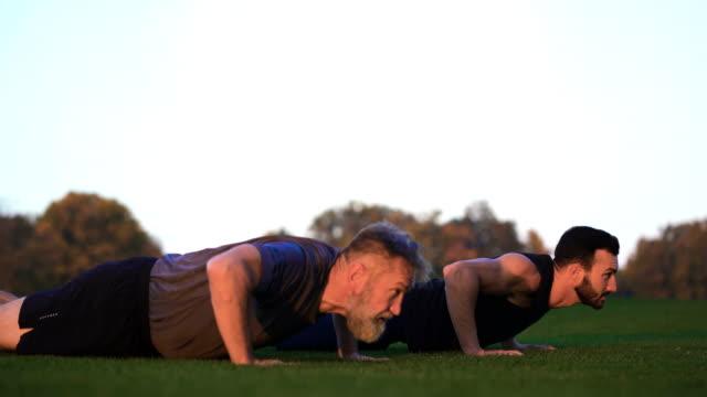 fadern och sonen som pressar upp gräset - styrketräning bildbanksvideor och videomaterial från bakom kulisserna