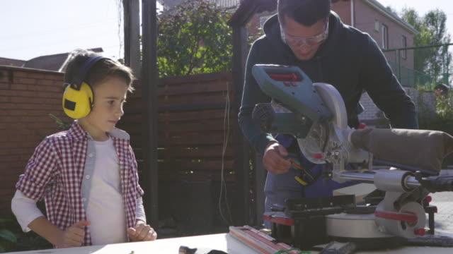 vídeos y material grabado en eventos de stock de el padre y su pequeño hijo haciendo carpintería al aire libre. cámara lenta - tablón