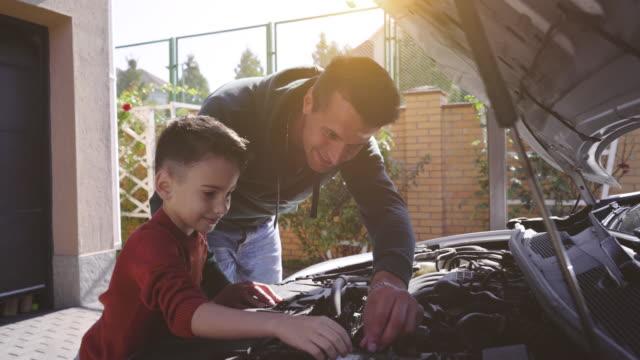 vídeos de stock e filmes b-roll de the father and son checking the car - capuz