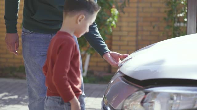vídeos de stock e filmes b-roll de the father and son checking under the car hood - capuz