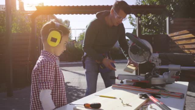 vídeos y material grabado en eventos de stock de el padre y el hijo haciendo carpintería juntos. cámara lenta - tablón