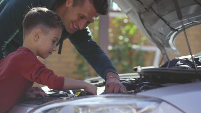 The father and son fixing the car. slow motion The father and son fixing the car. slow motion father stock videos & royalty-free footage