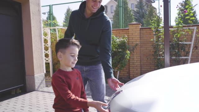 vídeos de stock e filmes b-roll de the father and son looking under the car hood - capuz