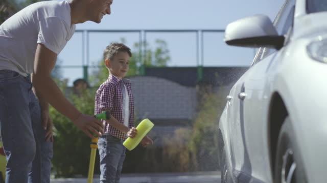 ホースパイプとスポンジで車を洗う父と息子。スローモーション - 援助点の映像素材/bロール