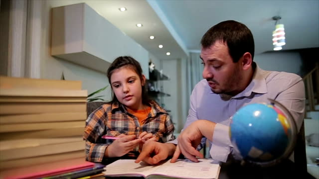 The father helps his daughter to do homework. Parent helps his child video