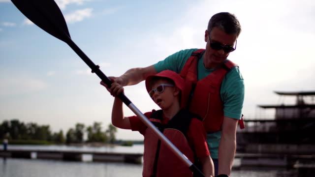 fadern lär sonen till rad i en kajak - flod vatten brygga bildbanksvideor och videomaterial från bakom kulisserna