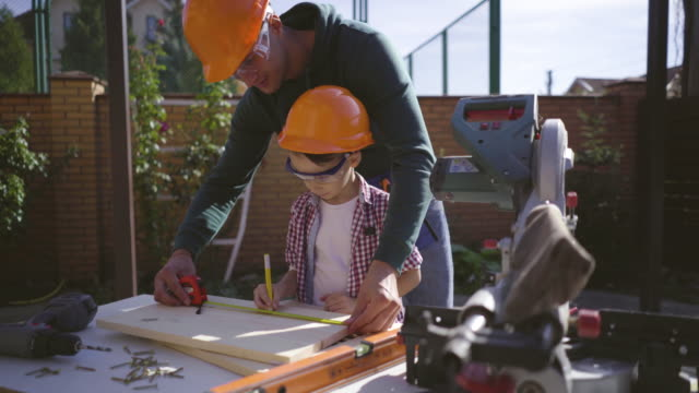 The father teaching his little son carpentry The father teaching his little son carpentry power tool stock videos & royalty-free footage