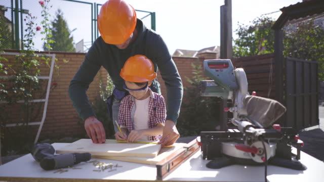der vater lehrt seinen kleinen sohn, werkzeuge zu benutzen - bauholz brett stock-videos und b-roll-filmmaterial