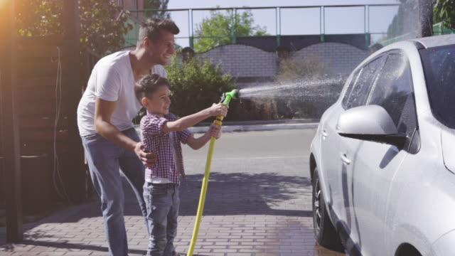 vidéos et rushes de le père avec son fils lavant la voiture. ralenti - laver