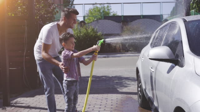 the father with his son washing the car. slow motion - myć filmów i materiałów b-roll