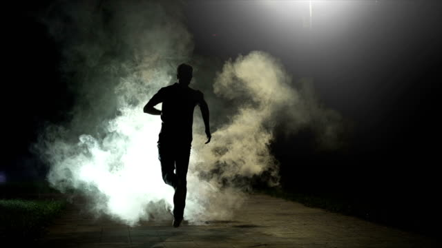 the fellow running in the cloud of smoke on the dark background, slow motion - fuggitivo video stock e b–roll