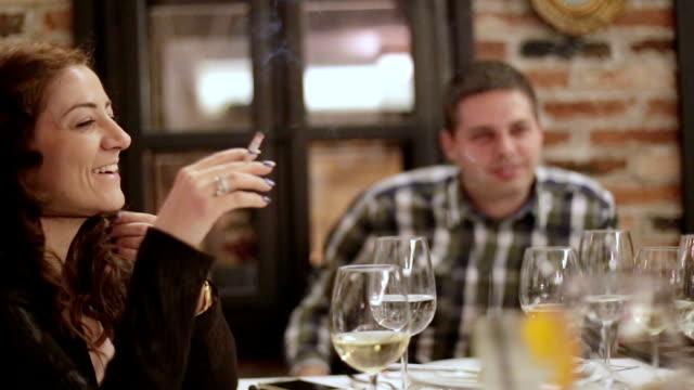la femmina fuma al ristorante con marito felice - sigaretta video stock e b–roll