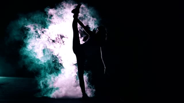 the female standing in twine in the smoke cloud. night time, slow motion - flessibilità video stock e b–roll
