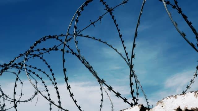 vídeos y material grabado en eventos de stock de la cerca con alambre de púas en el fondo de un cielo azul oscuro nublado sombrío. - valla límite