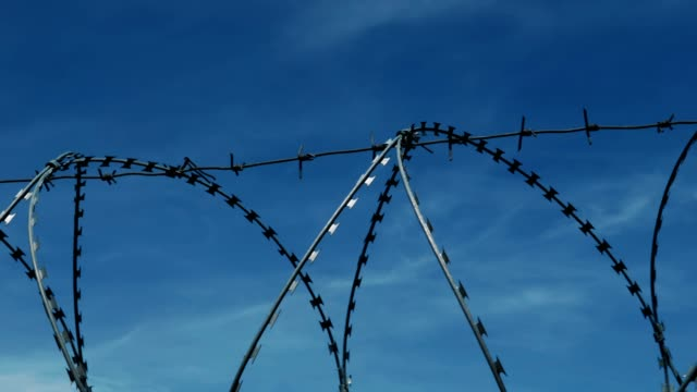 The fence with barbed wire on the background of a gloomy cloudy dark blue sky.