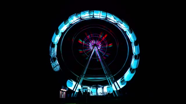 la ruota panoramica in luci al neon di filatura veloce, time lapse - luna park video stock e b–roll
