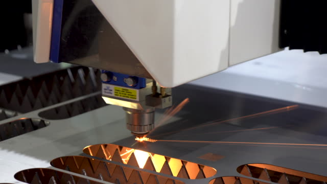 The fiber laser cutting machine cutting the sheet metal plate with the sparking light. Hi-technology manufacturing concept.