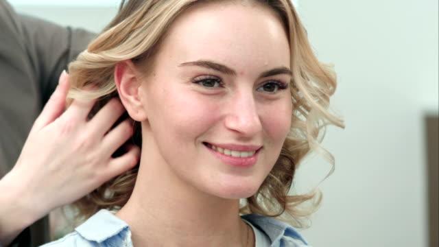 final de estilo de pelo rizado de modelo de peluquería en el salón de belleza. - vídeo