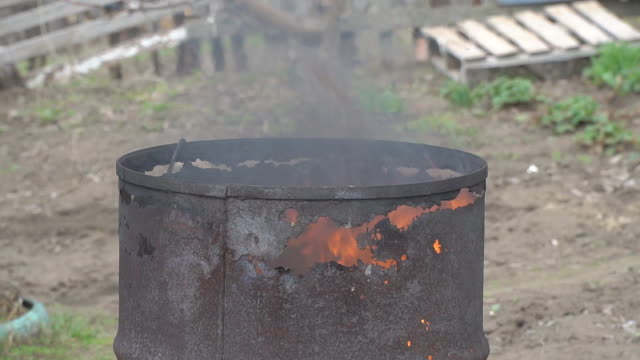 the fire burns in an old rusty barrel - cask video stock e b–roll