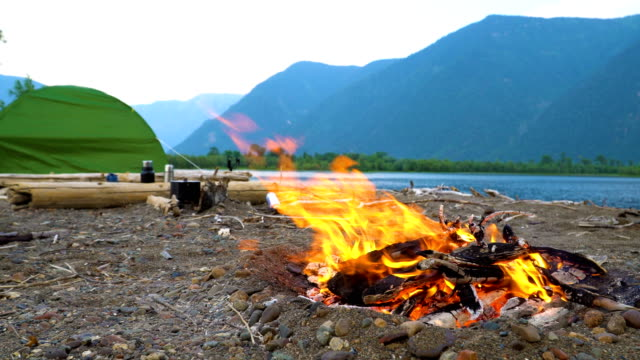The fire burns on the shore of a mountain lake. video