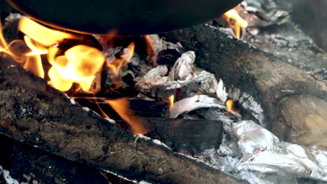 The fire is kindling under the cauldron The fire is burning under the cauldron where lunch is being prepared. bonfire stock videos & royalty-free footage