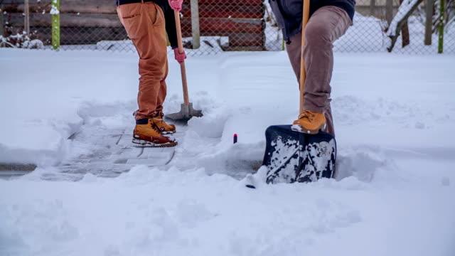 den första människan har avslutat sin rast och nu skotta tillbaka snö - skyffel bildbanksvideor och videomaterial från bakom kulisserna