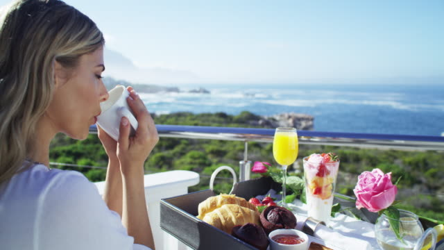 The first meal of the day with a difference 4k video footage of a young woman having coffee and breakfast while relaxing on the balcony of a beach house indulgence stock videos & royalty-free footage