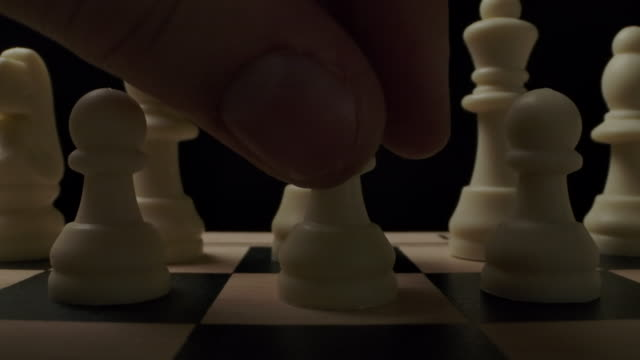 vídeos de stock e filmes b-roll de the first standard move by white chess pawn on checker board - xadrez