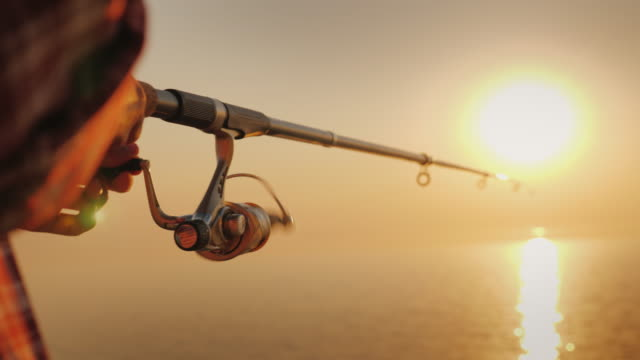 The fisherman's hands, holds the spinning rod, rotates the coil handle. Hobby and activity video