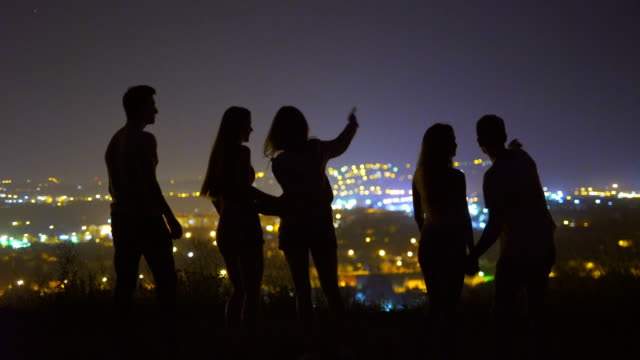 The five people stand on the background of the city. evening night time