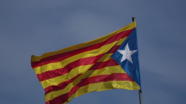 vídeos de stock, filmes e b-roll de a bandeira de catalonia que acena no vento em um fundo do céu azul. - setembro amarelo
