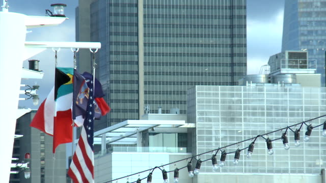 The flags fluttering on the ship. Buildings in the background