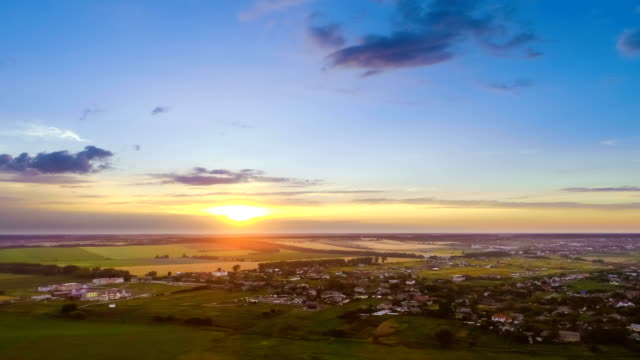 the flight above the town on a sunrise background. quadrocopter shot, time lapse - небольшой город стоковые видео и кадры b-roll