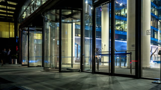 the flow of people passing through the revolving door of the modern office building at the end of the working day,time lapse - entrata video stock e b–roll