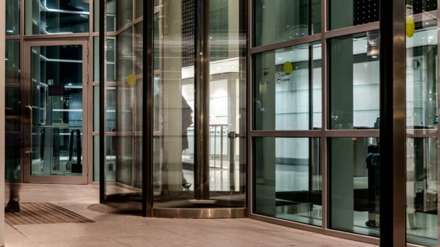 The flow of people passing through the revolving door of the modern office building at the end of the working day,time lapse