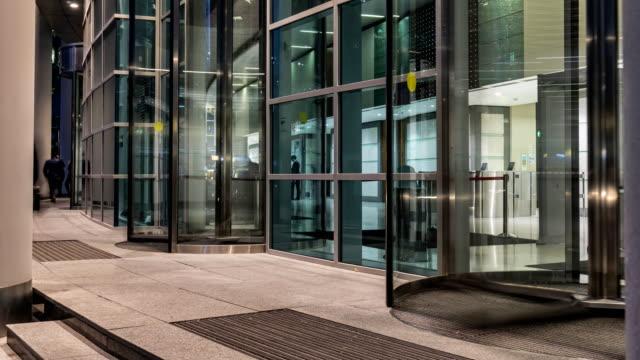 vidéos et rushes de le flux de personnes passant par la porte tournante de l'immeuble de bureaux moderne à la fin de la journée de travail, laps de temps - porte entrée