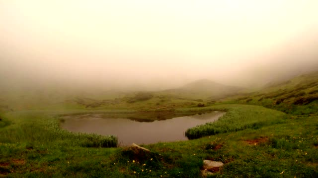 The Fog Absorbs a Small Lake in The Mountains video