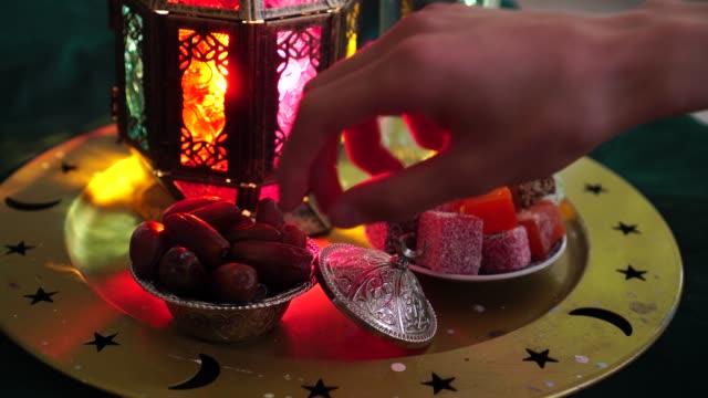 maten av ramadan. glas vatten, dadlar, torkade frukter, godis. en man äter datum för att bryta den snabba - ramadan lykta bildbanksvideor och videomaterial från bakom kulisserna