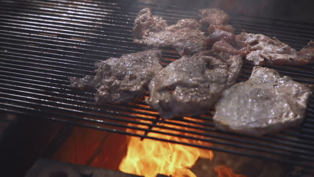 The footage of barbecue beef pork is burnt by the hot ember of burning wood log fire