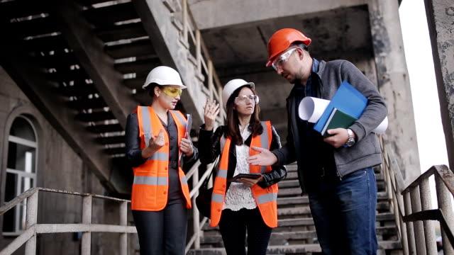 av förman och två kvinnor inspektörer för att diskutera planen för arbete som utförs på konstruktion eller restaurering av byggnaden. - construction workwear floor bildbanksvideor och videomaterial från bakom kulisserna