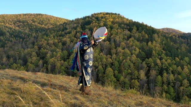 The forest shaman knocks on a tambourine and dances a ritual dance. The forest shaman knocks on a tambourine and dances a ritual dance. HD minority groups stock videos & royalty-free footage