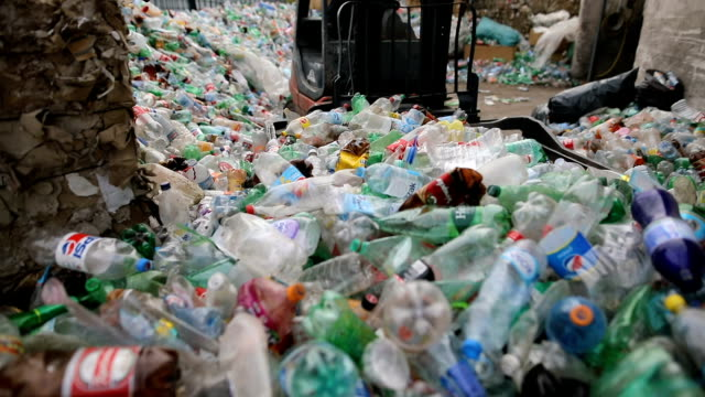 The forklift puts packaged plastic bottles on a pile.Working at a recycling factory video