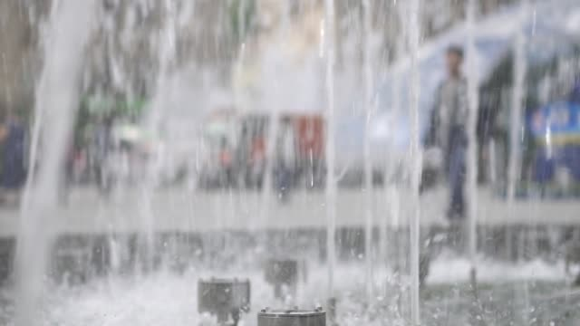 The fountain in the city is close-up. Water jets slowed down. City street summer video