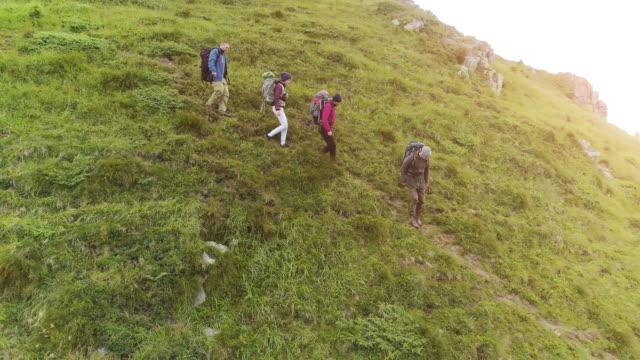 vídeos de stock e filmes b-roll de the four hikers with backpacks walking down on the mountain - estrada urbana