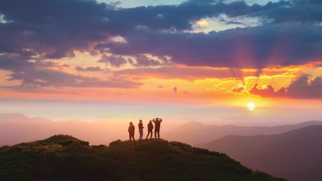 stockvideo's en b-roll-footage met de vier mensen die op een berg met een mooie zonsondergang dansen - vier personen